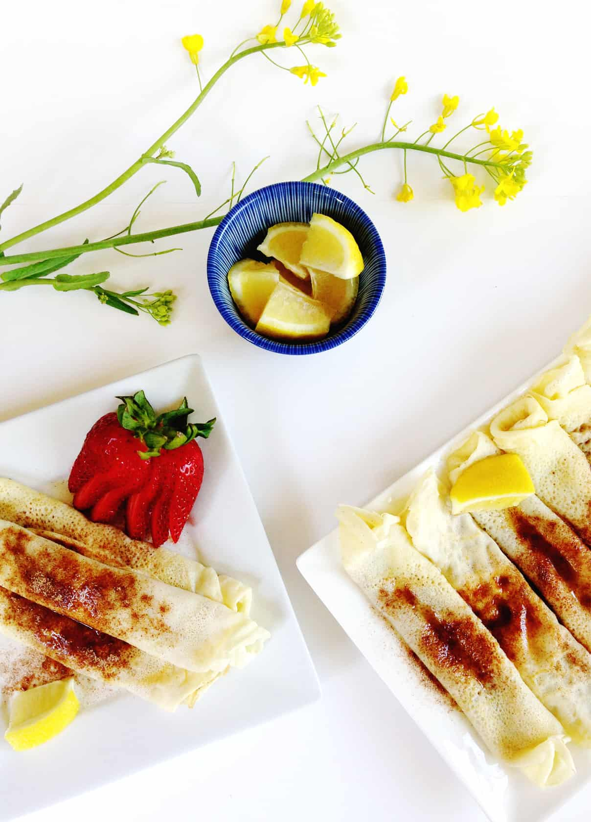 two plates with south african pannekoek pancakes and garnished with lemon wedges and fresh strawberries