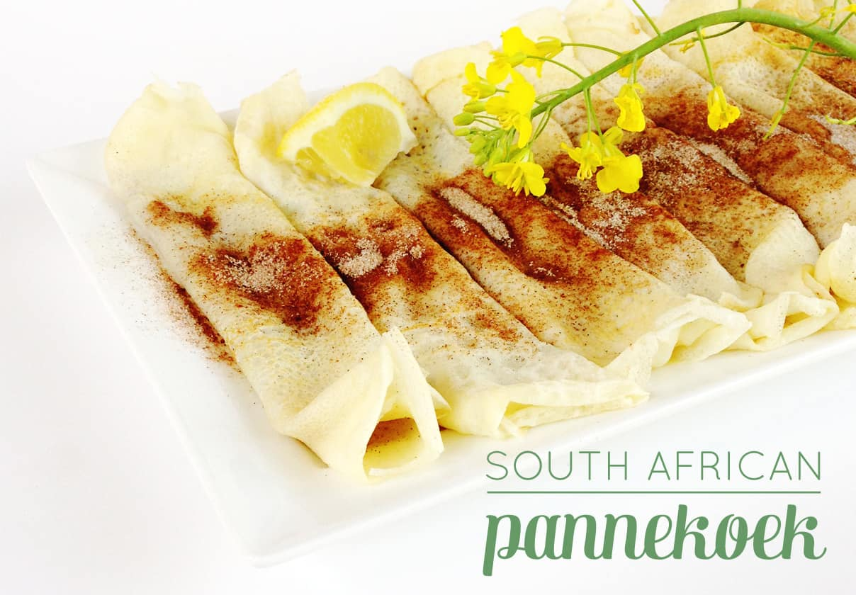 thin south african pancakes rolled up and topped with cinnamon sugar and lemon juice, and a yellow flower for garnish