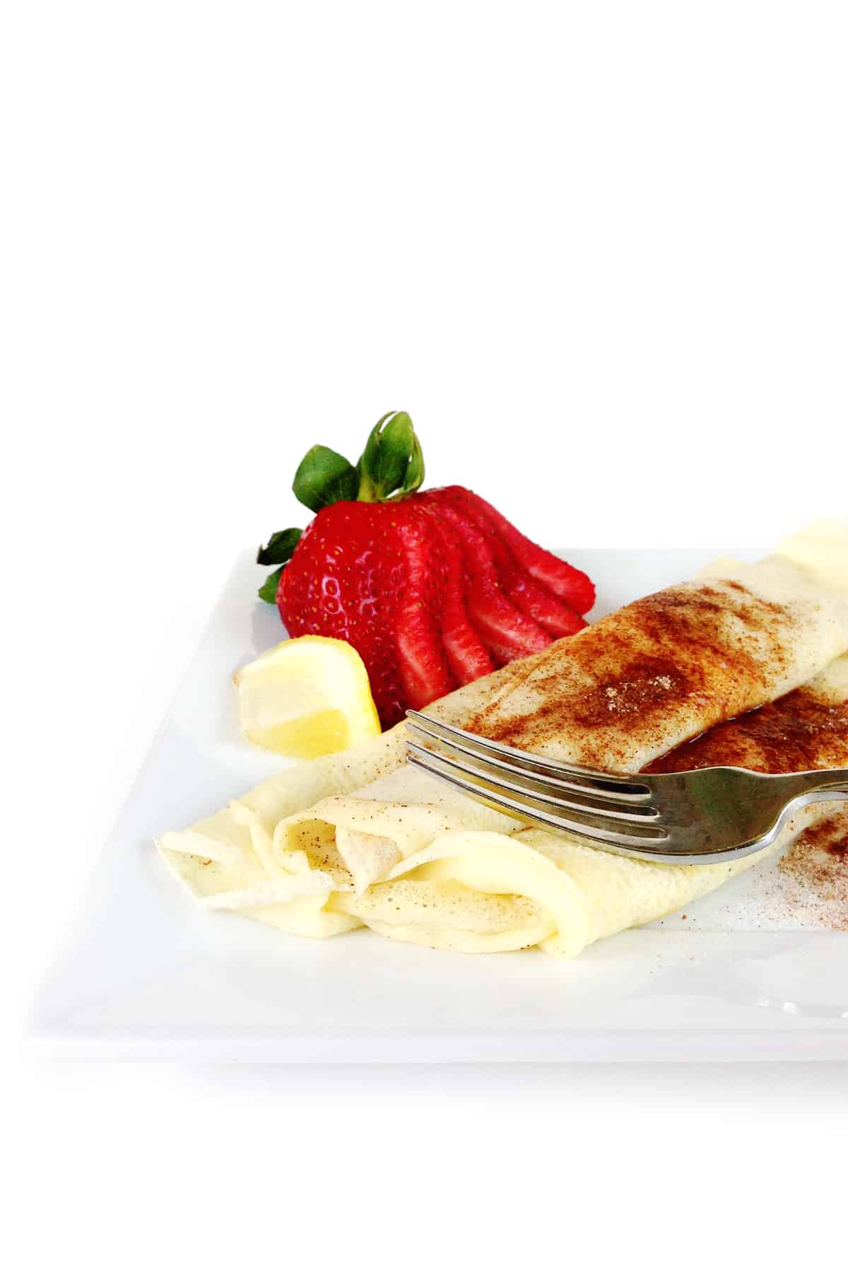 south african pannekoek on a white plate with a lemon wedge and a sliced strawberry