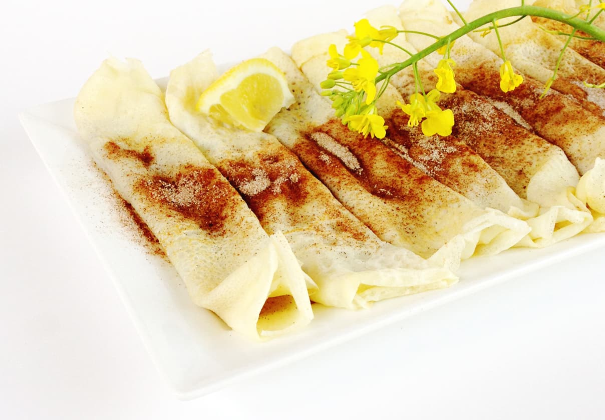 a white ceramic tray with rolled up south african pannekoek adorned with cinnamon sugar