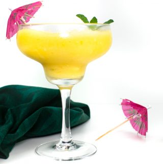 frozen mango daiquiri with a pink parasol and a green tea towel
