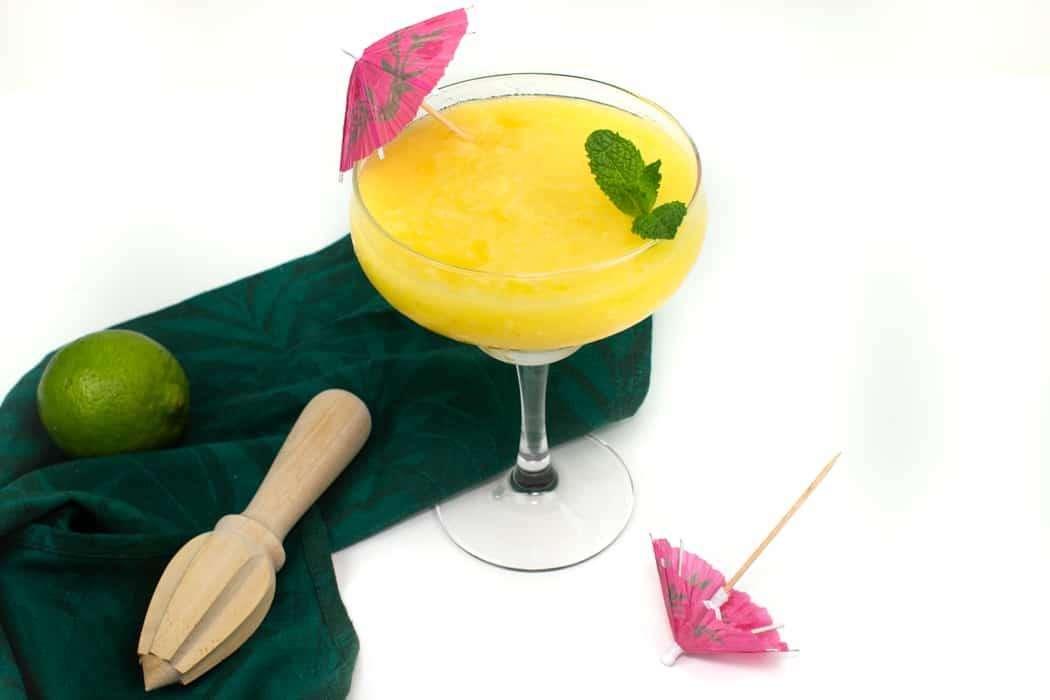 frozen mango daiquiri with a pink parasol and a green tea towel