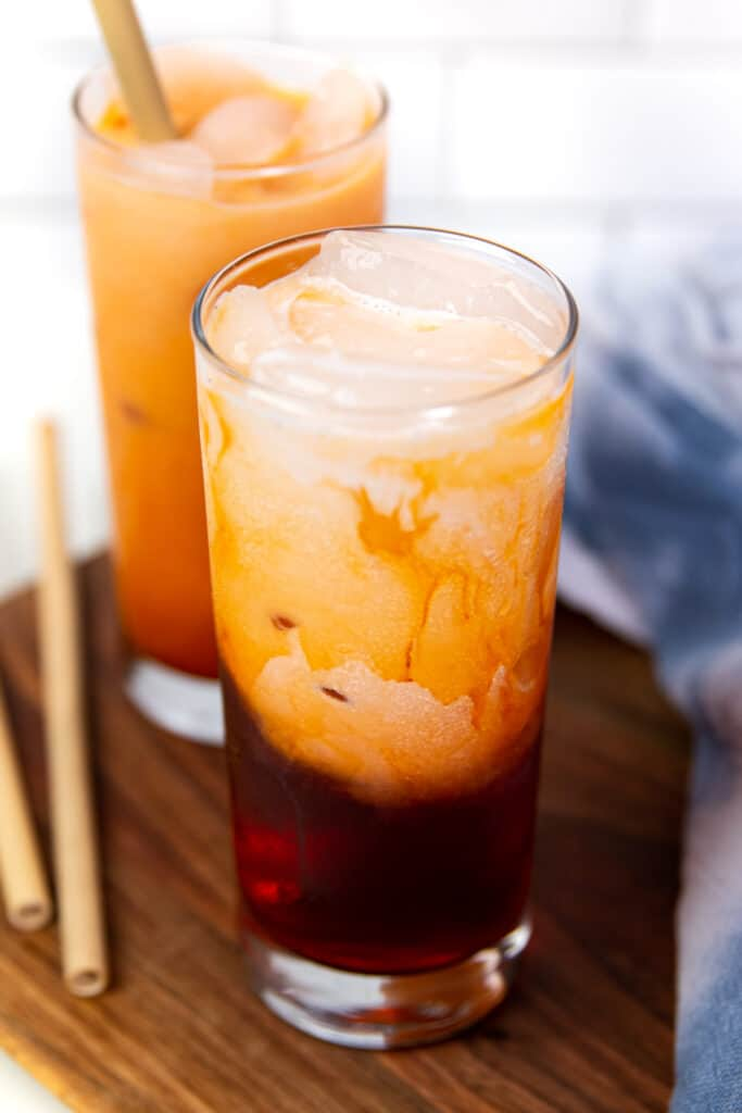 two glasses of spiked thai iced tea with milk on a wooden board