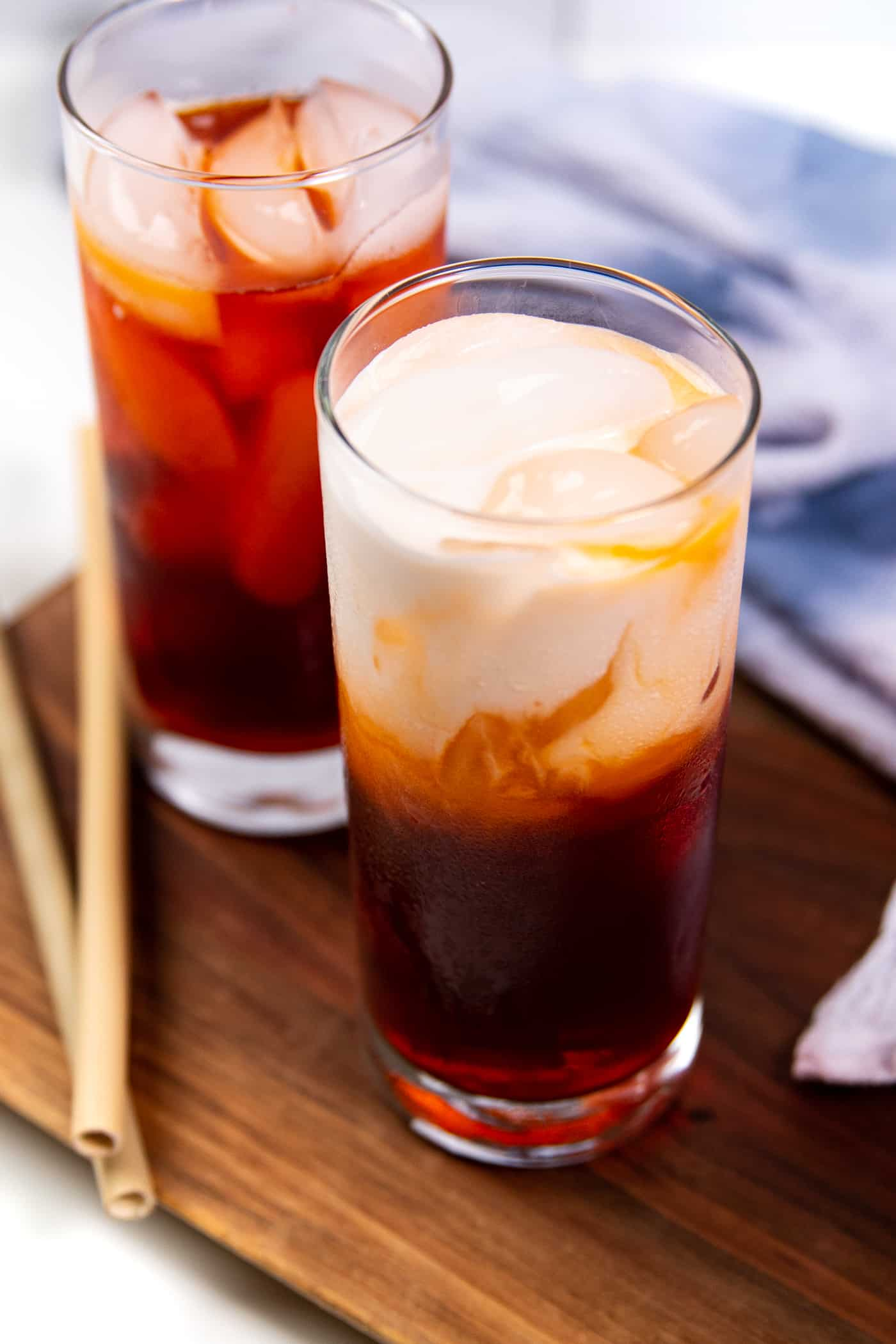 a glass of thai iced tea with a layer of cream on top