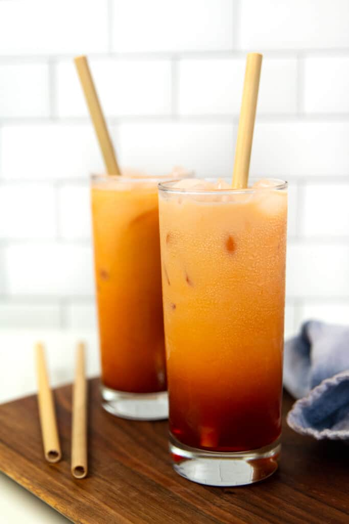 two glasses of spiked thai iced tea on a wooden board next to a blue tea towel