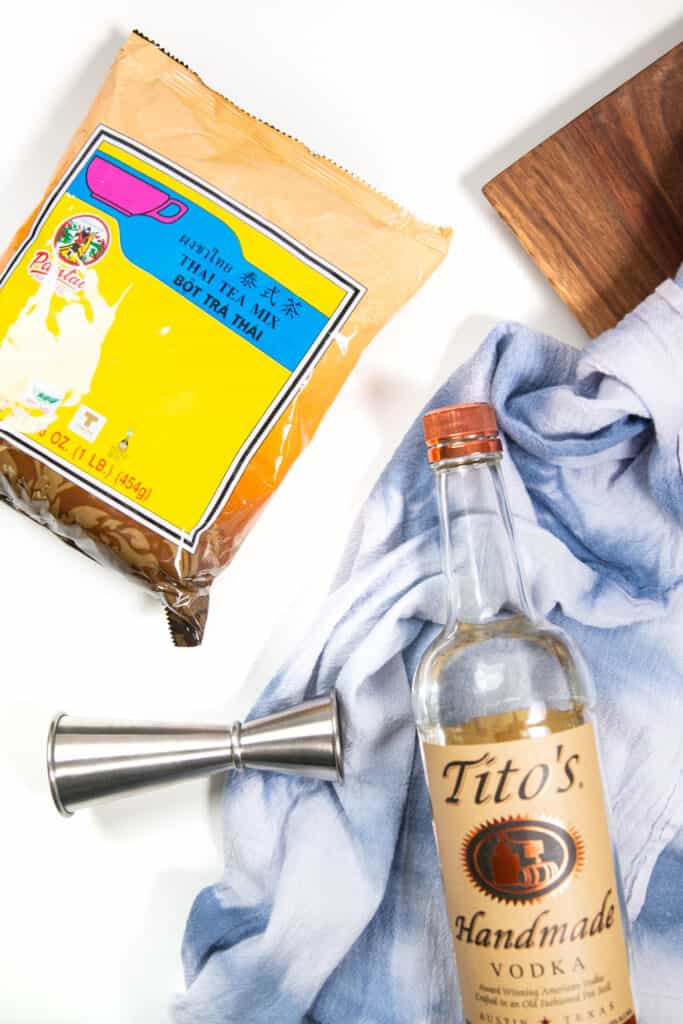 a flat lay photo of the makings of spiked thai iced tea, including a bag of thai tea mix, a jigger, a bottle of vodka and a blue tea towel