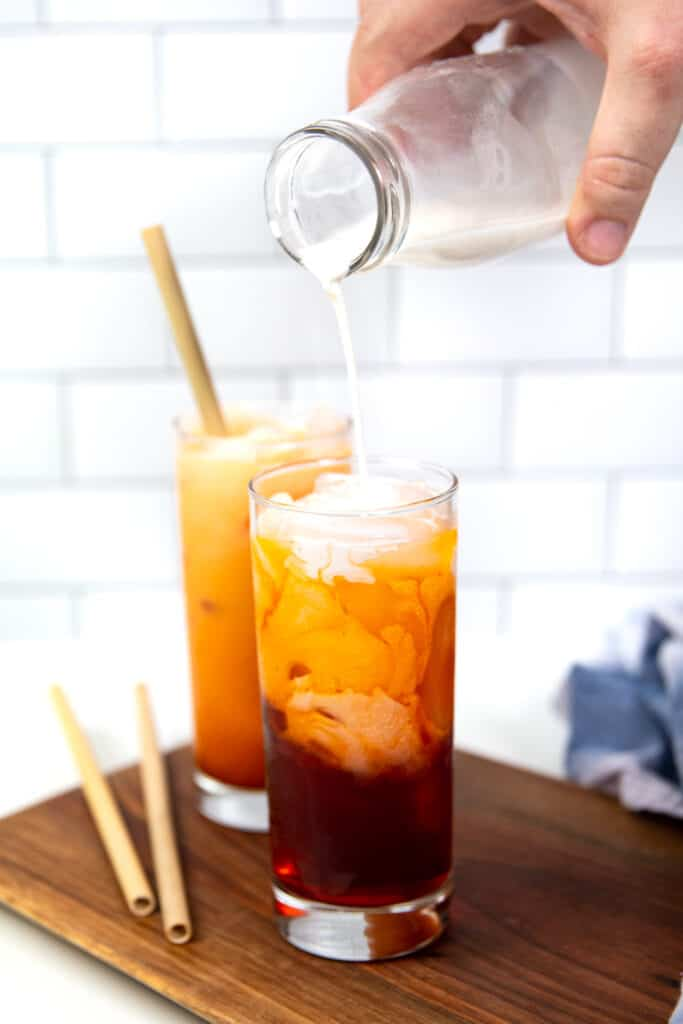 a hand pouring milk into a glass of spiked thai iced tea