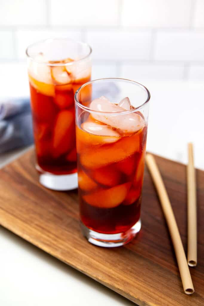 two glasses of thai iced tea on a wooden board