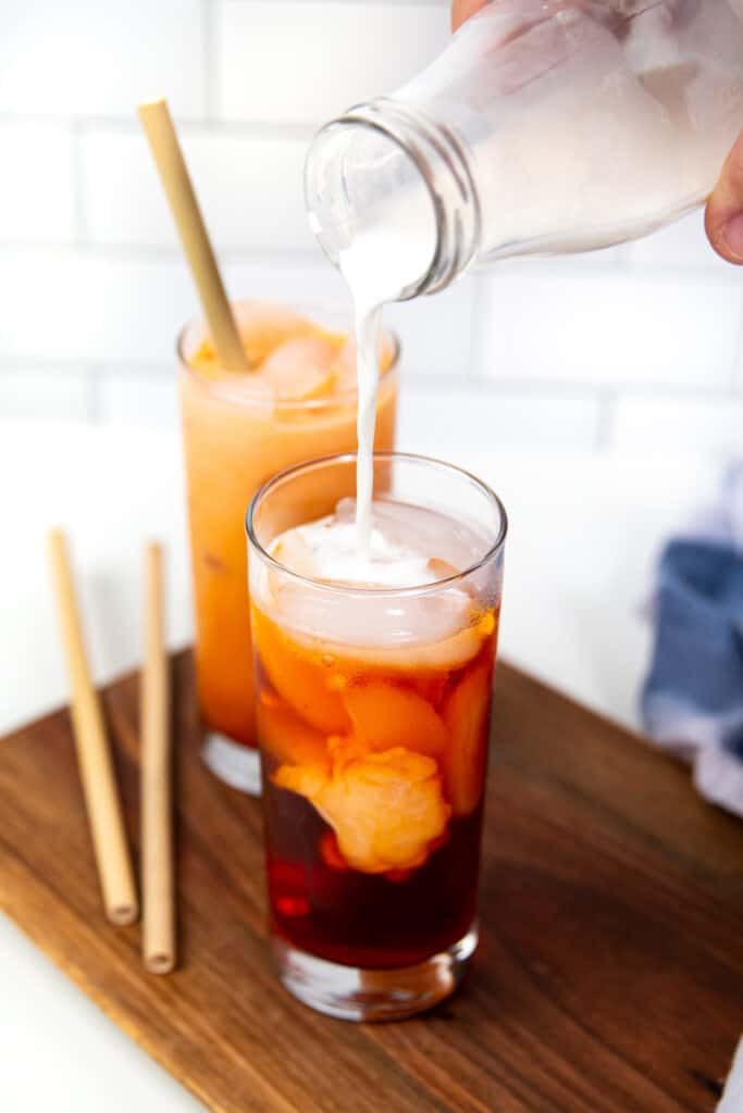 a hand pouring milk from a glass milk jar into a glass of thai iced tea