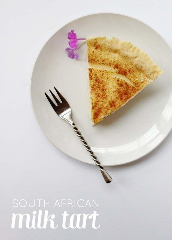 a slice of milk tart on a white plate and garnished with a purple flower
