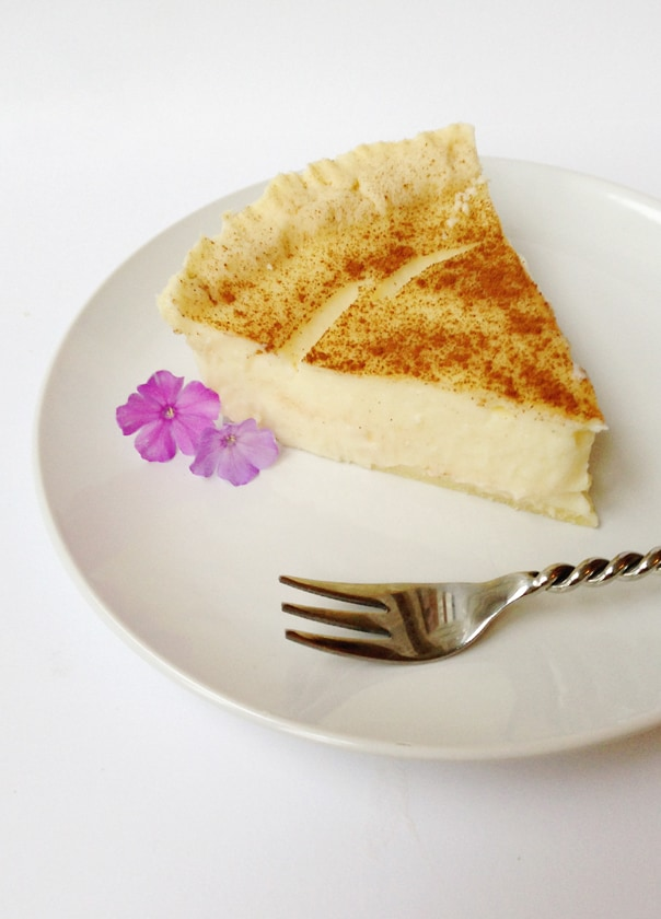 a white plate with a slice of milk tart and a silver fork