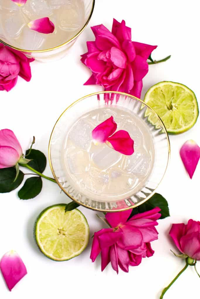 above shot of elderflower rose gimlets with pink garden roses and limes