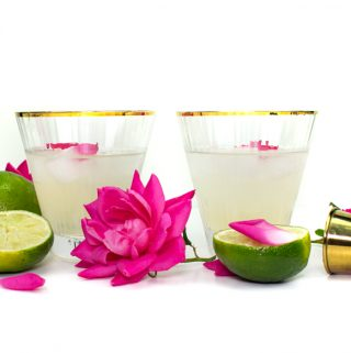 two elderflower rose gimlets in a gold-rimmed stemless cocktail glass with pink garden roses and limes on a white background