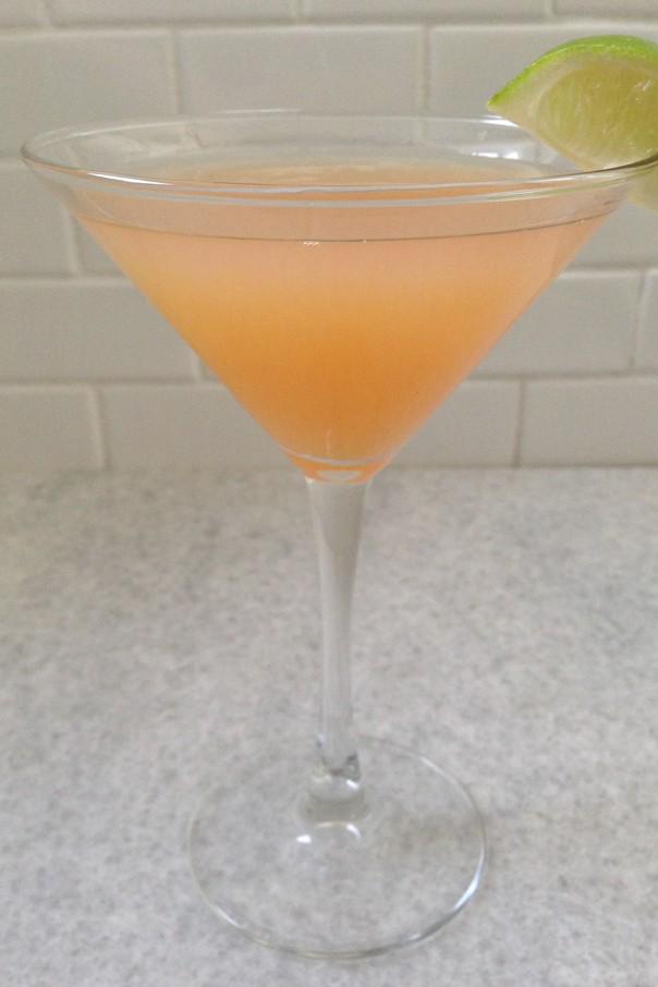 Guava Cosmopolitan in a martini glasson a marble slab