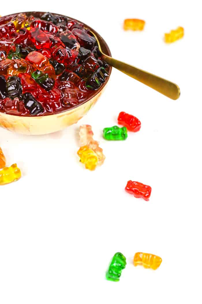 a gold spoon dipping into a bowl of drunken gummy bears