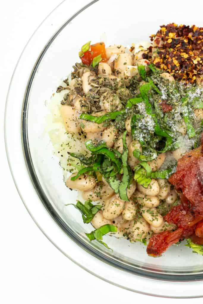 white beans, herbs and tomatoes in a clear glass bowl