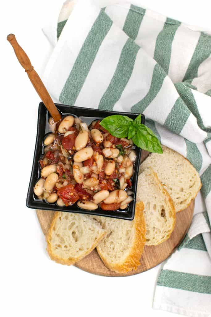 a black square bowl containing tuscan white bean dip next to a platter of fresh bread