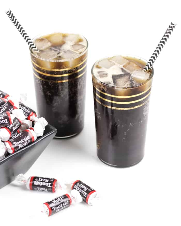 two tootsie roll cocktails with black and white striped straws and tootsie roll candies