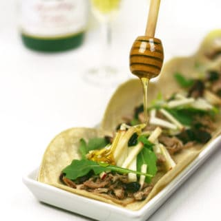 Holiday Apple Cider Pulled Pork Tacos are an easy meal to make at the holidays. Use a crock pot or slow cooker to cook pork flavored with spices and Martinelli's Apple Cider or Juice. Serve it on tortillas with apple matchsticks, dried cranberries, arugula and honey for an offbeat, festive holiday meal. (via feastandwest.com)