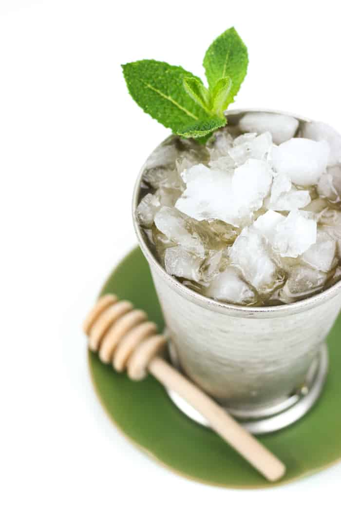a honey whiskey mint julep garnished with a mint sprig in a silver julep cup on a green plate with a honey wand