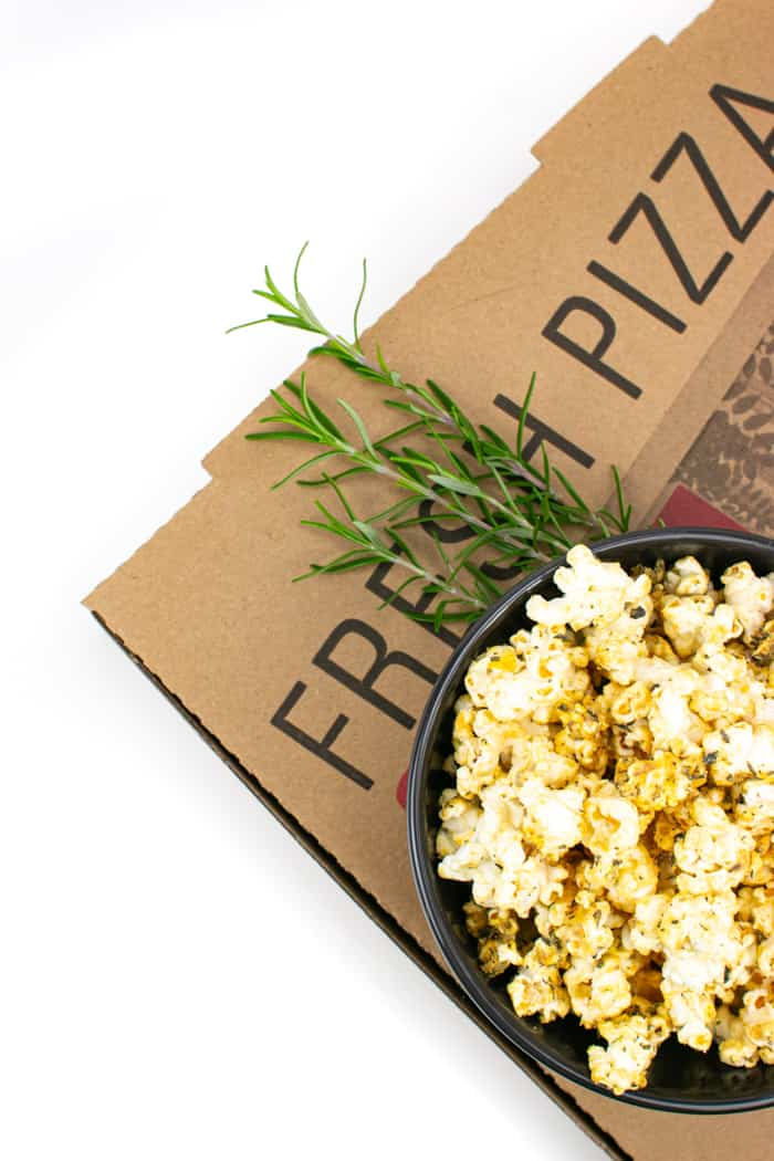 Pizza popcorn in a bowl with fresh rosemary and a pizza box