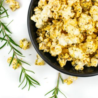 Pizza popcorn in a bowl with fresh rosemary