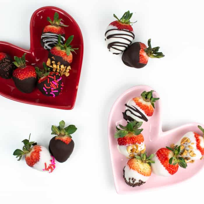 chocolate covered strawberries arranged on a pink heart shaped plate and a red heart shaped plate
