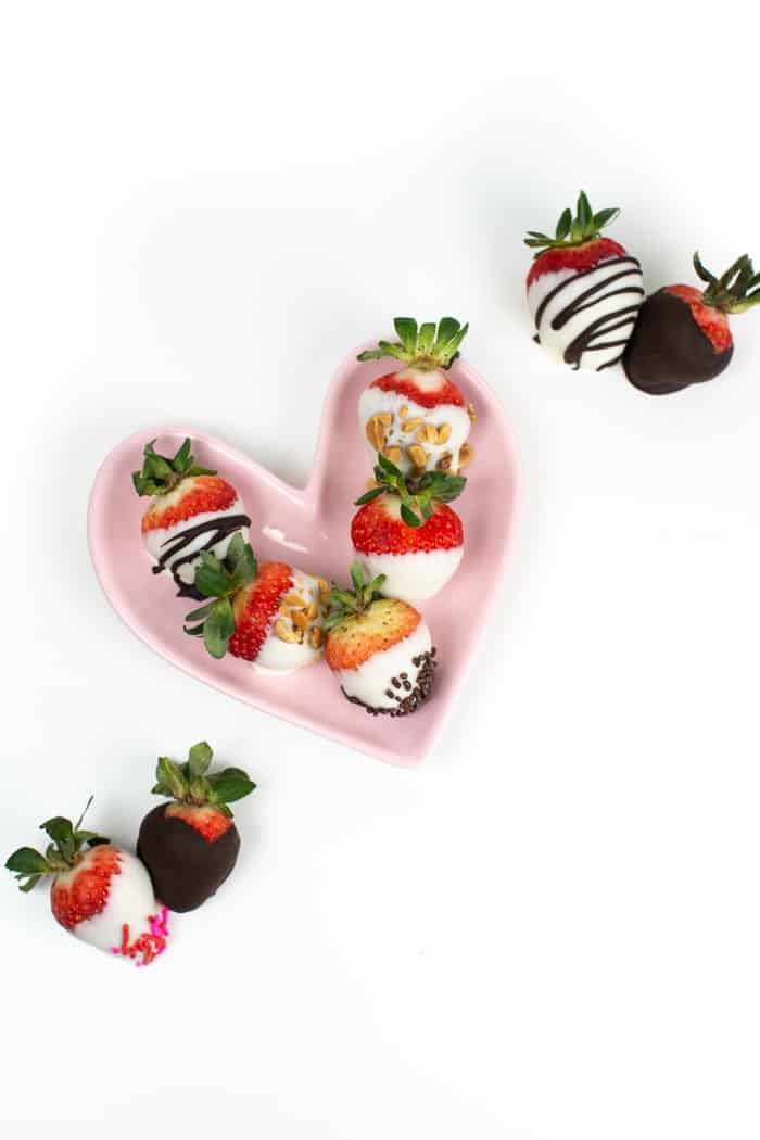 chocolate covered strawberries arranged on a pink heart shaped plate