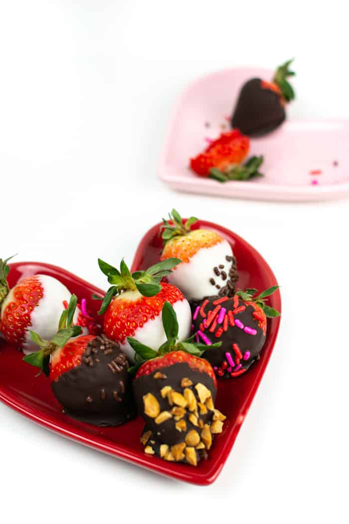 several kinds of chocolate covered strawberries on a heart shaped plate