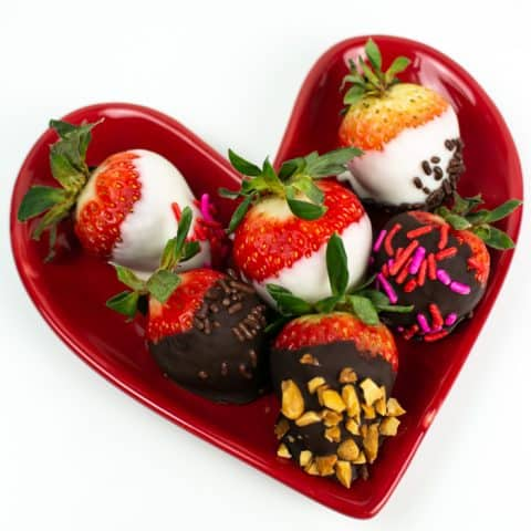 an assortment of chocolate covered strawberries on a red heart shaped plate