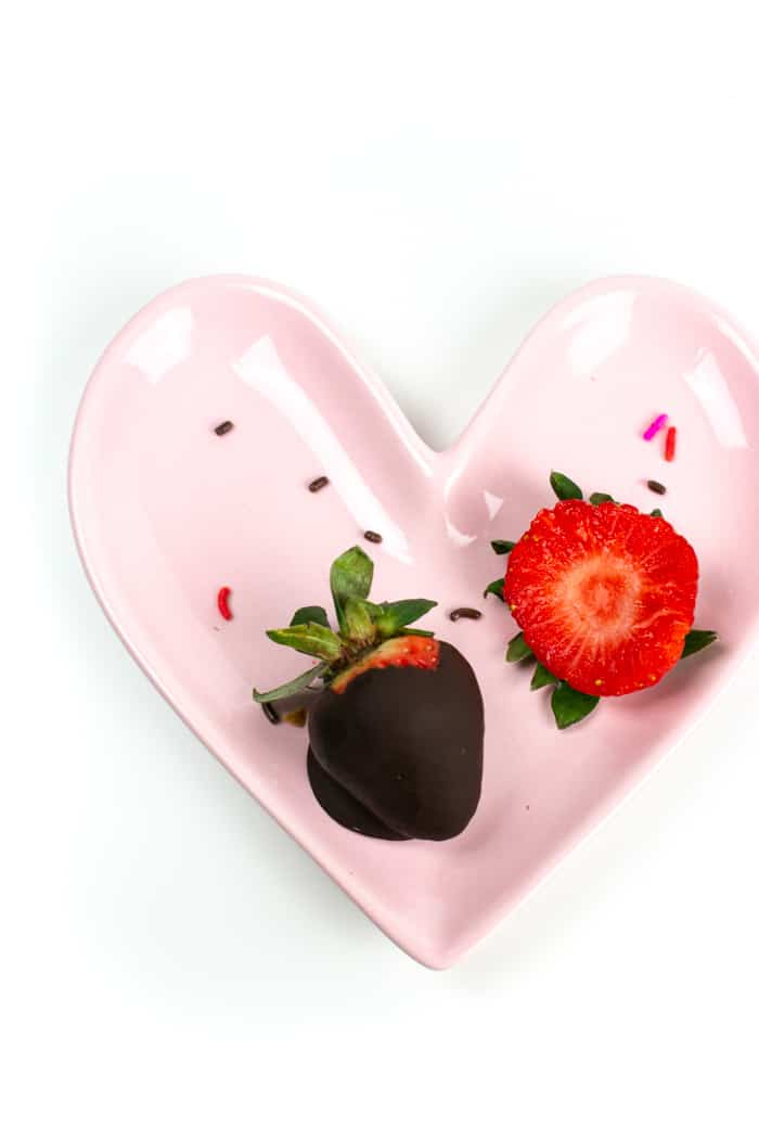 one eaten and one uneaten chocolate covered strawberries on a pink heart shaped plate