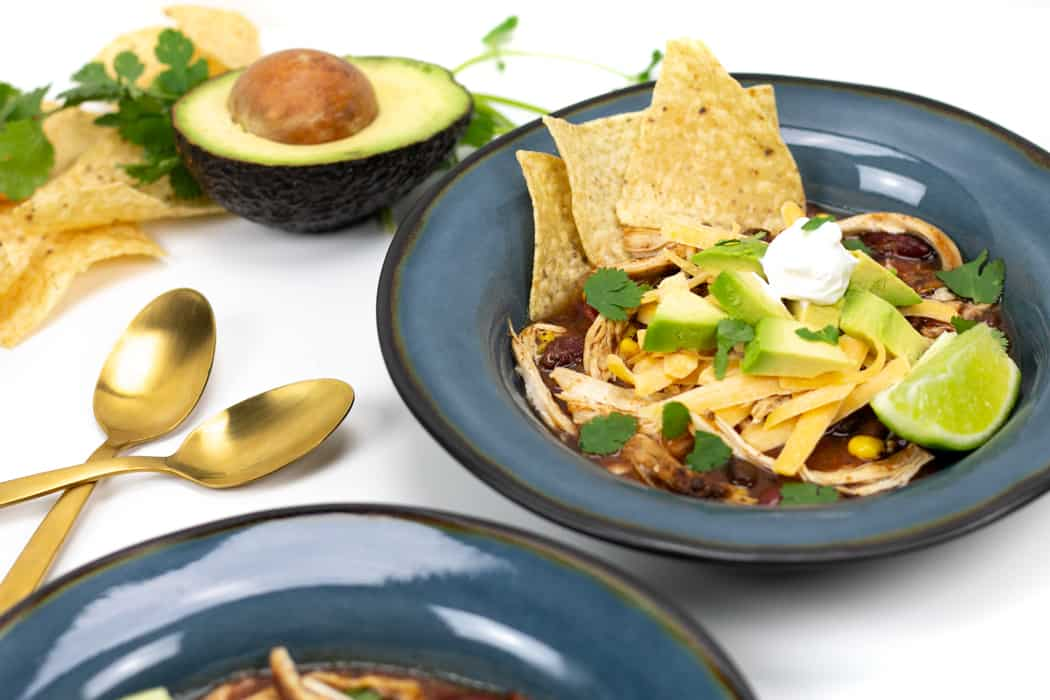 two blue bowls of easy chicken tortilla soup on a table