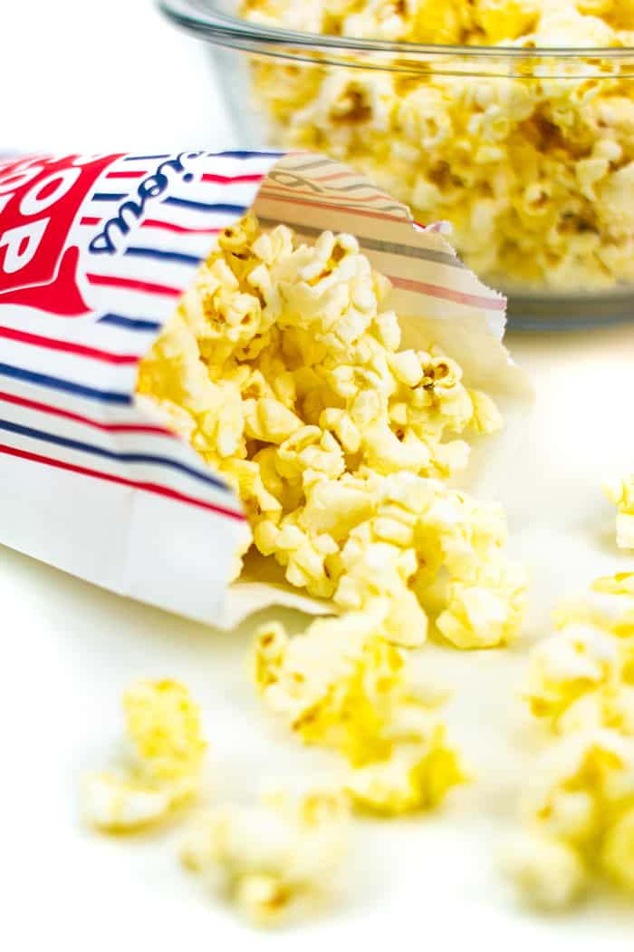 movie theatre butter popcorn in a popcorn bag next to a bowl of popcorn