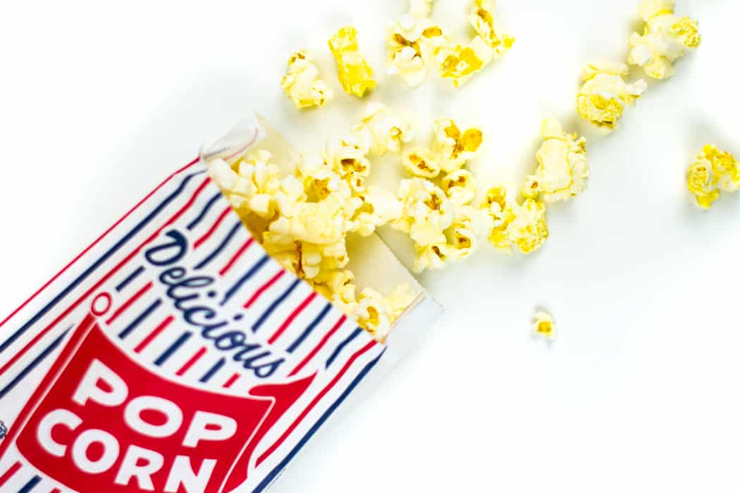 movie theatre butter popcorn spilling out of a popcorn bag
