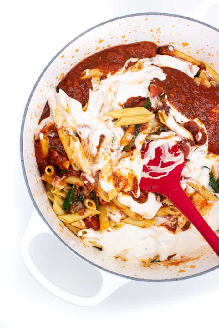 Stirring together marinara and alfredo sauce to make rosa sauce