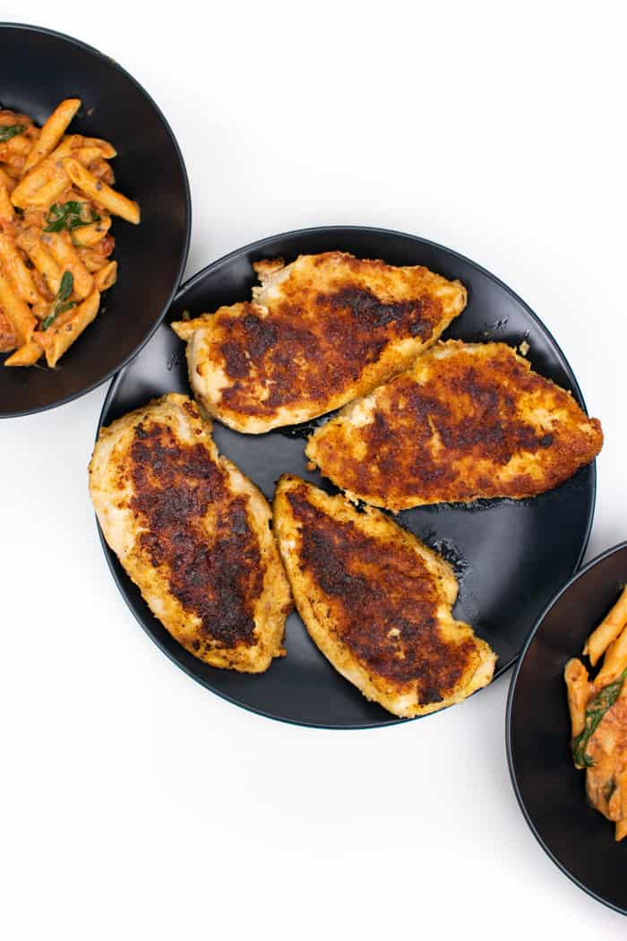 image of golden parmesan crusted chicken and plates of penne rosa
