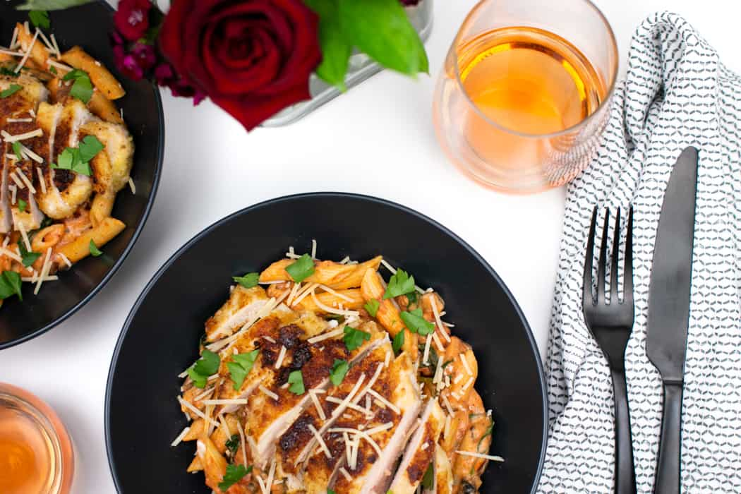 finished plates of parmesan crusted chicken with penne rosa and rosé wine