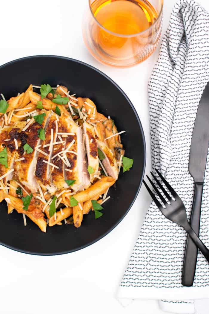 a plate of penne rosa and parmesan crusted chicken with a fork and knife and a glass of rosé wine