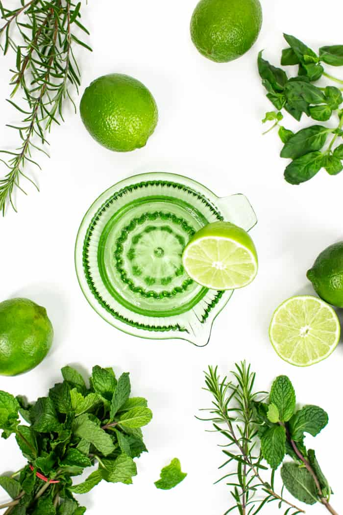 prep shot of green glass citrus juicer with fruits and herbs