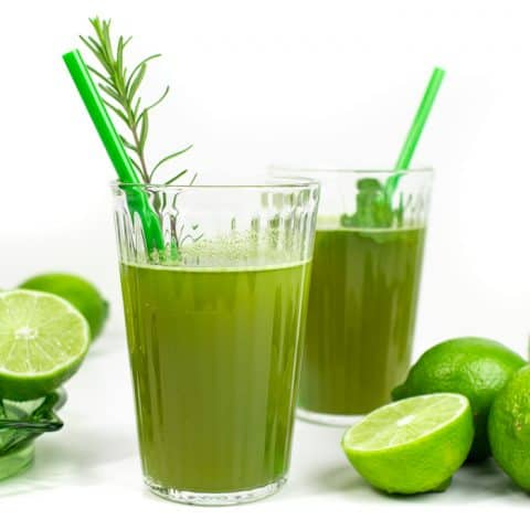 two glasses of herbal limeade with green straws and limes
