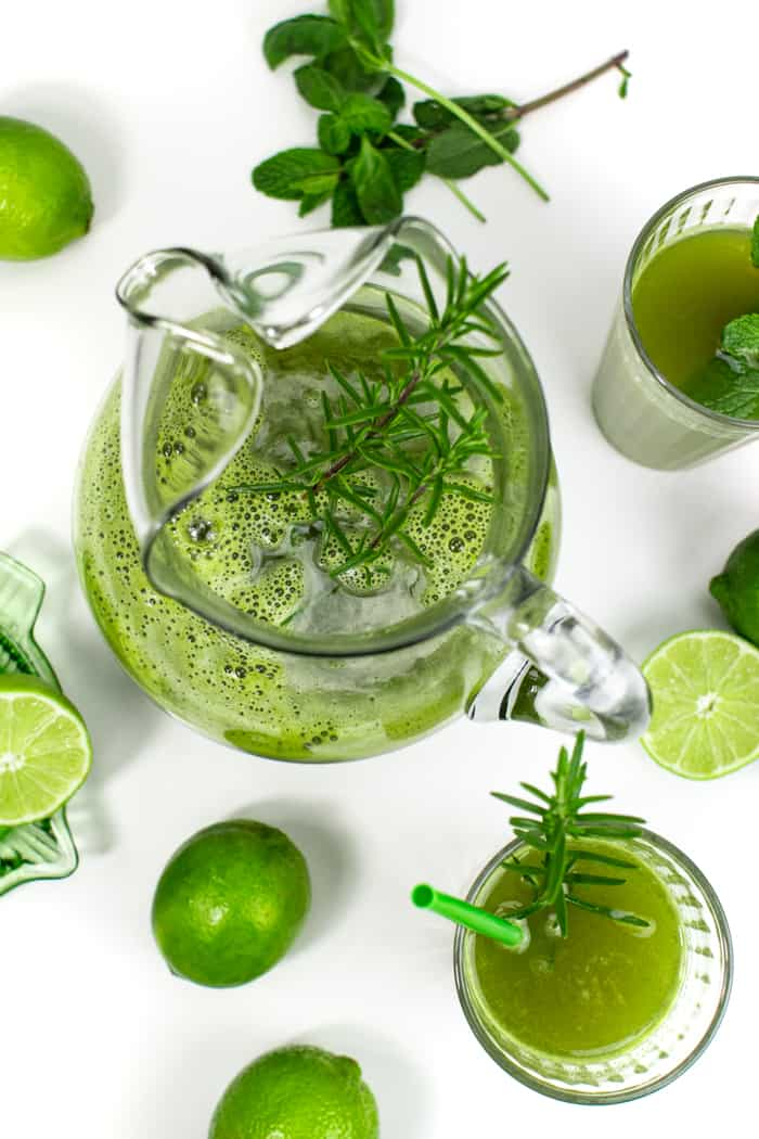 a top down view of a pitcher of herbal limeade, glasses of herbal limeade and limes