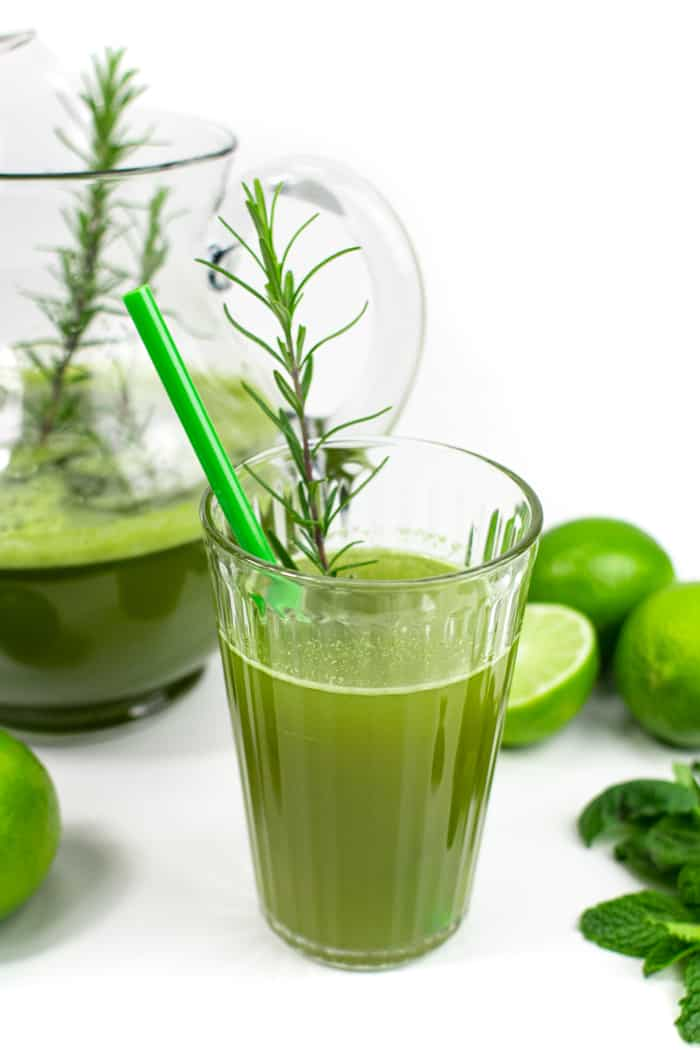 a glass of herbal limeade with green straw next to a pitcher and limes
