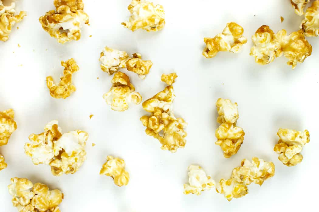 caramel popcorn kernels on a white surface