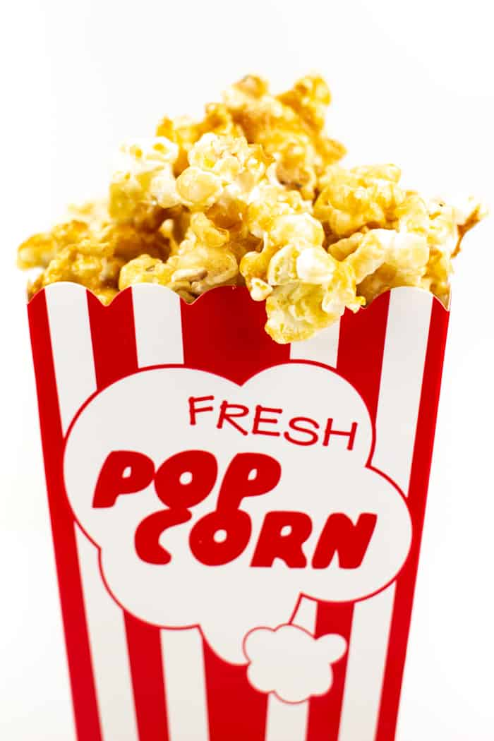 closeup of a red and white popcorn container filled with a caramel popcorn recipe