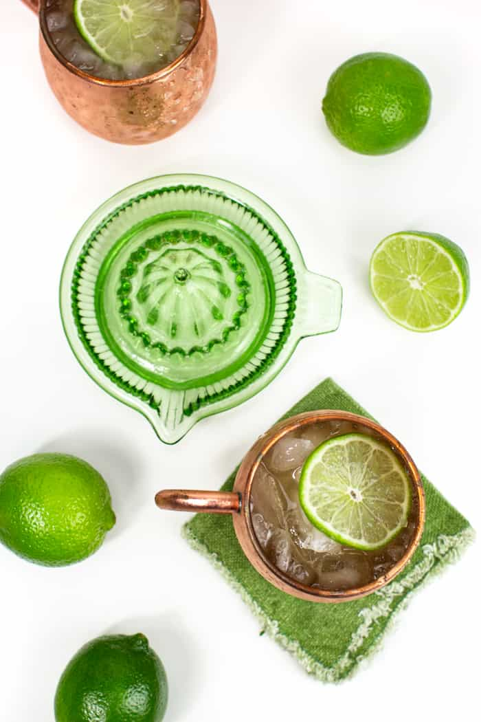picture of bourbon ginger ale cocktails on green napkins and a green citrus juicer