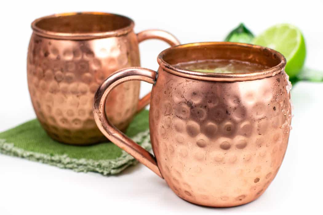 two irish mule cocktails in copper mugs