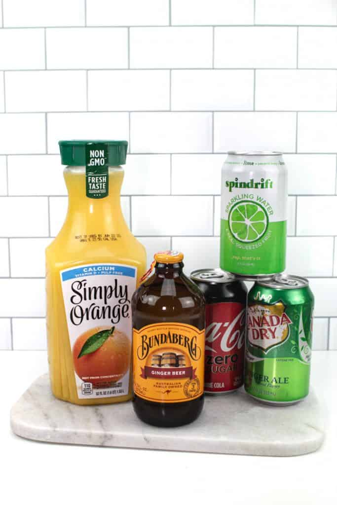 bottles of common mixers such as orange juice, ginger beer, soda, sparkling water and ginger ale