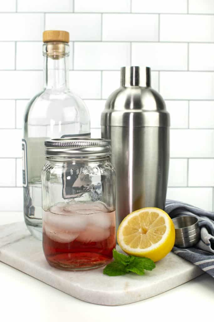 a bottle, mason jar and cocktail shaker
