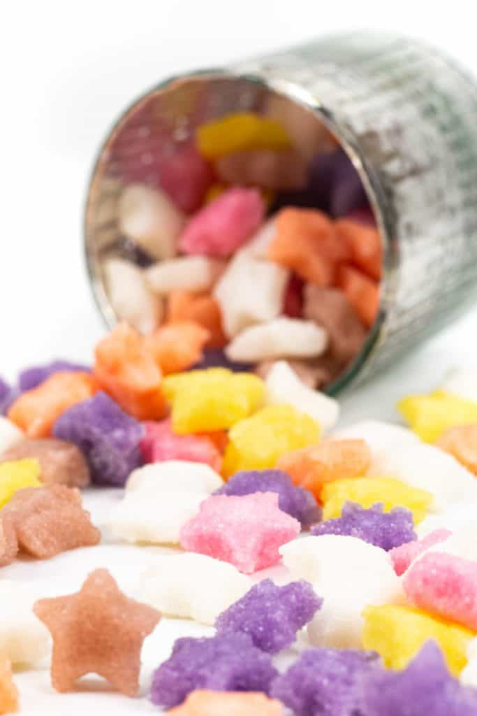 colored sugar cubes spilling out of a silver cup