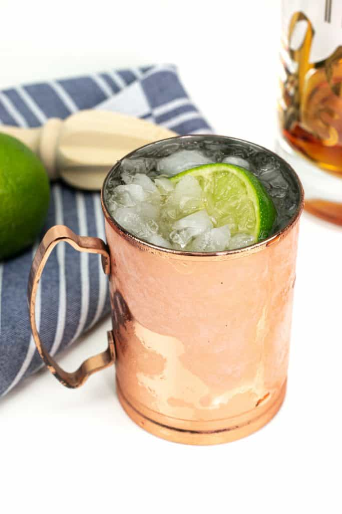 kentucky mule next to a decanter of whiskey in a copper mule mug